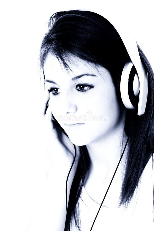 Muchacha adolescente hermosa con los auriculares en tonos azules imágenes de archivo libres de regalías