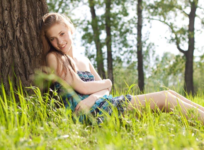 Muchacha adolescente hermosa en alineada azul en el prado fotos de archivo