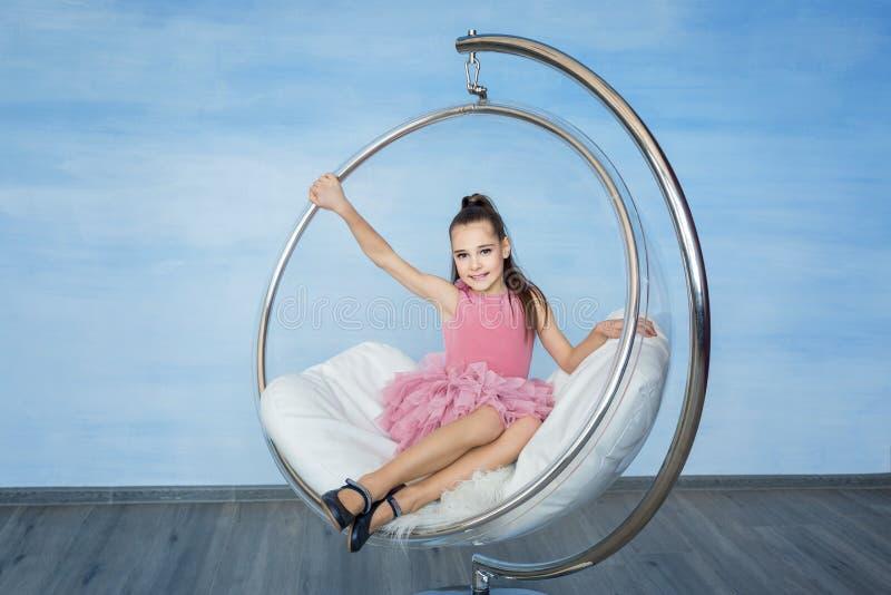 Muchacha adolescente hermosa en un vestido rosado que se sienta en silla de cristal redonda fotografía de archivo