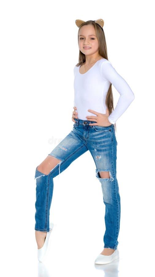 Muchacha adolescente hermosa en vaqueros con los agujeros imagen de archivo