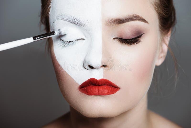 muchacha adolescente hermosa joven que aplica el bodyart blanco creativo con el cepillo del maquillaje en cara, fotografía de archivo libre de regalías