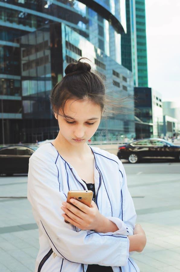 Muchacha adolescente hermosa que goza de un smartphone fotos de archivo