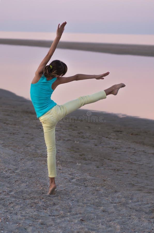 Muchacha adolescente hermosa que hace un elemento de la danza en el fondo del mar en la puesta del sol, foto de archivo libre de regalías