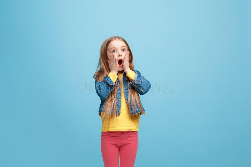 Muchacha adolescente hermosa que parece sorprendida aislado en azul fotografía de archivo libre de regalías