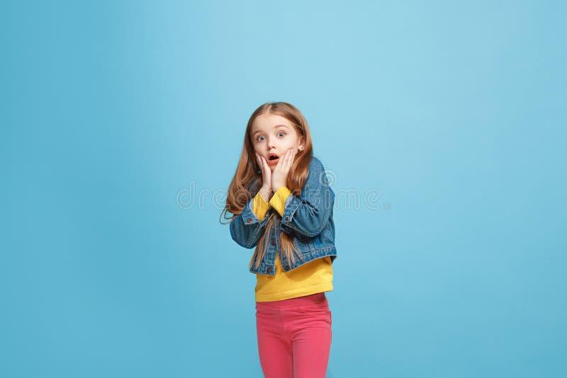 Muchacha adolescente hermosa que parece sorprendida aislado en azul imagen de archivo