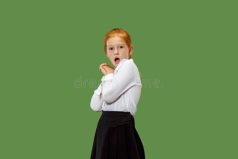 Muchacha adolescente hermosa que parece sorprendida aislado en verde imágenes de archivo libres de regalías