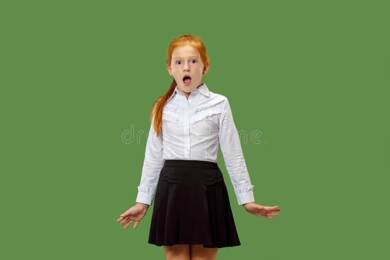 Muchacha adolescente hermosa que parece sorprendida aislado en verde foto de archivo