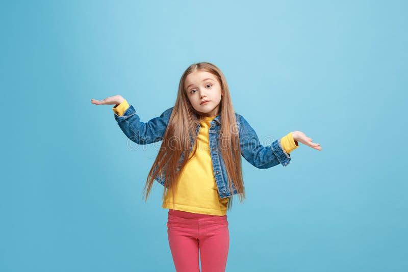 Muchacha adolescente hermosa que parece sorprendida y desconcertar aislado en azul imagen de archivo