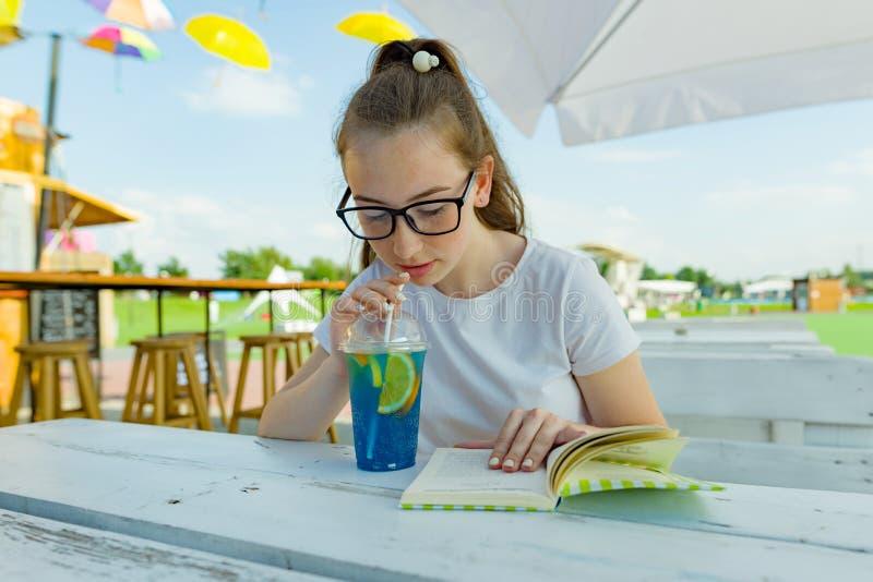 Muchacha adolescente joven con los vidrios que bebe la limonada y el libro de lectura azules en un café al aire libre Zona verde  fotografía de archivo libre de regalías