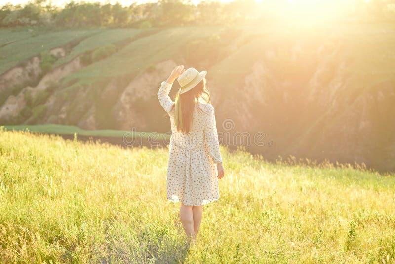 Muchacha adolescente joven feliz del estudiante que lleva un sombrero del vestido y de paja del verano en manos El caminar al air foto de archivo