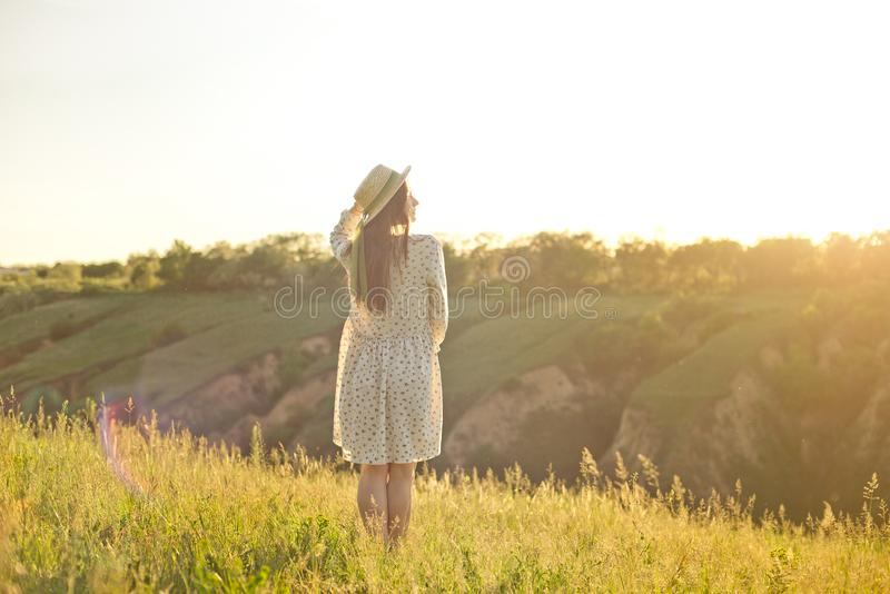 Muchacha adolescente joven feliz del estudiante que lleva un sombrero del vestido y de paja del verano en manos El caminar al air imagen de archivo libre de regalías