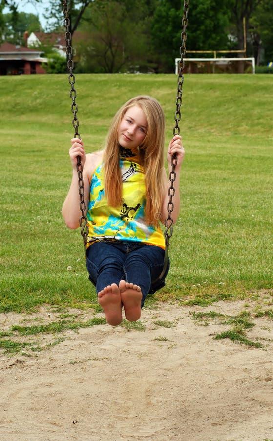 Muchacha adolescente joven que juega en un oscilación imagen de archivo