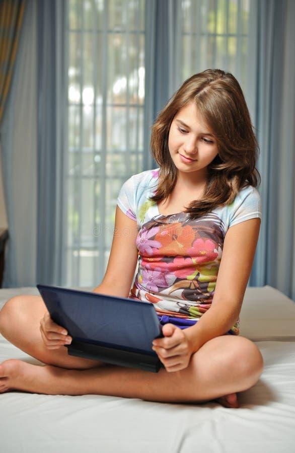 Muchacha adolescente joven que pone en su cama con el cuaderno fotos de archivo