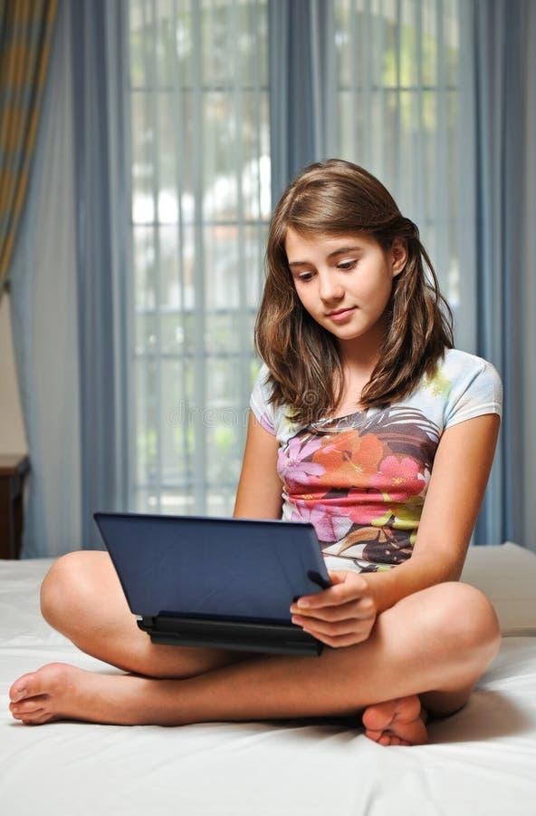 Muchacha adolescente joven que pone en su cama con el cuaderno foto de archivo libre de regalías