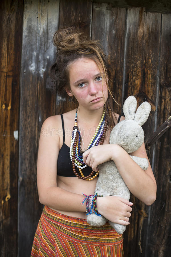 Muchacha adolescente joven triste con el conejo viejo del juguete en las manos en zonas rurales foto de archivo libre de regalías