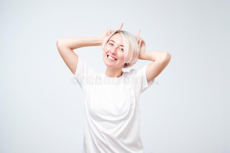 Muchacha adolescente juguetona con la camiseta coloreada del blanco de preparación del peinado que muestra los cuernos imagenes de archivo
