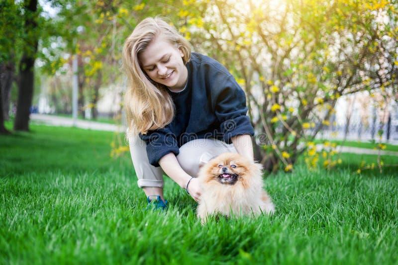 Muchacha adolescente linda con el pelo rubio que juega con su perrito de Pomeranian imagen de archivo libre de regalías