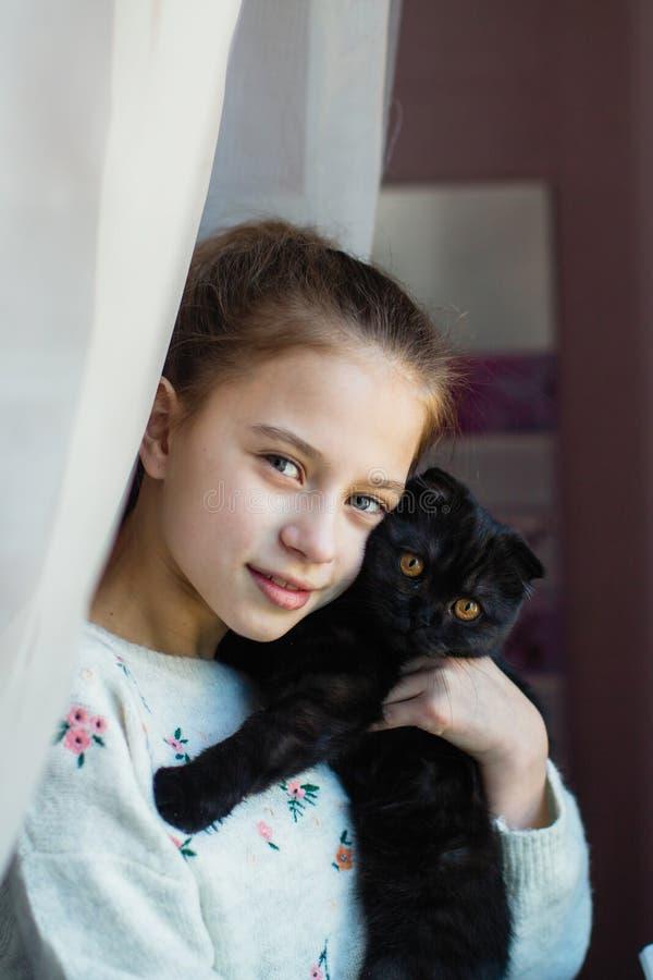 Muchacha adolescente linda que sostiene un gatito en sus brazos Amor foto de archivo