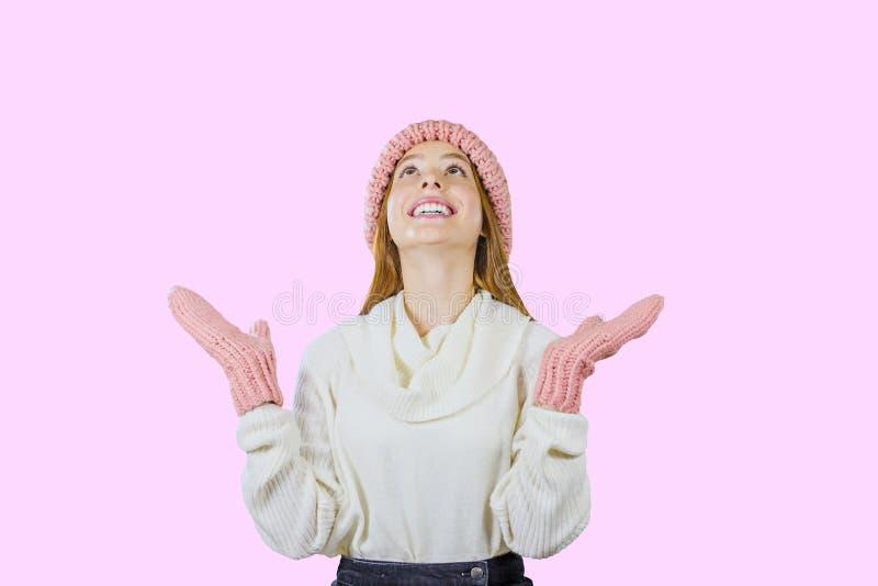 Muchacha adolescente pelirroja linda joven en un sombrero rosado hecho punto y las manoplas que levantan sus manos encima de mira imagenes de archivo