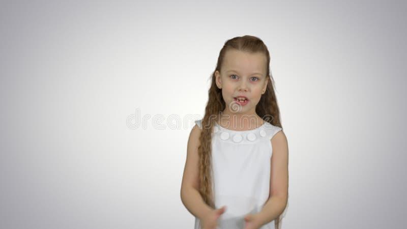 Muchacha adolescente positiva que habla con una cámara con una sonrisa en el fondo blanco imagen de archivo
