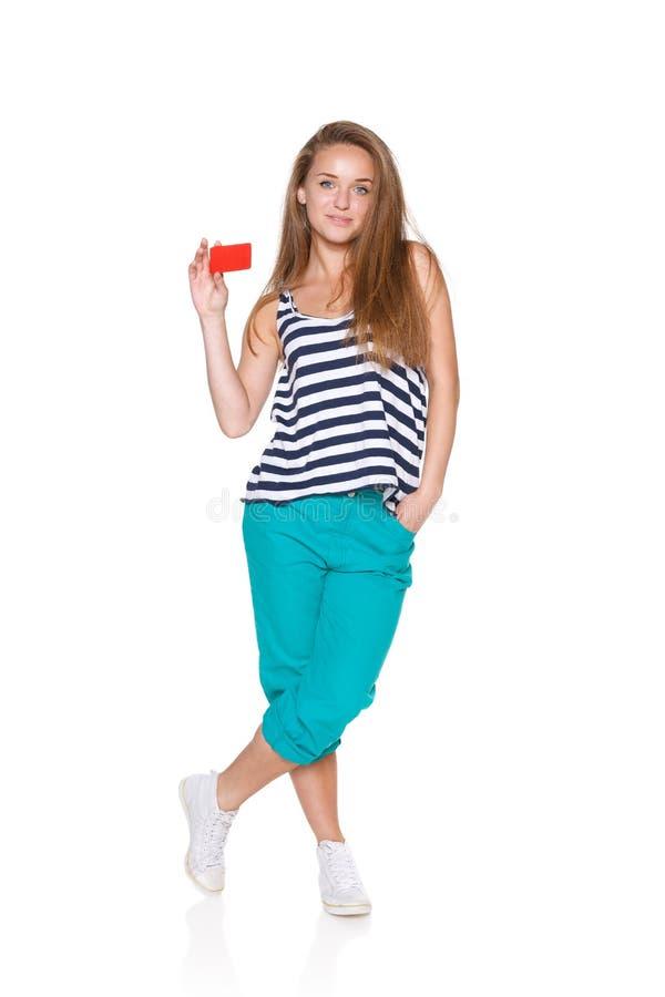 Muchacha adolescente positiva que sonríe mostrando la tarjeta de crédito imagen de archivo