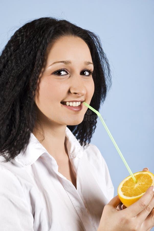 Muchacha adolescente que bebe una naranja fotos de archivo libres de regalías