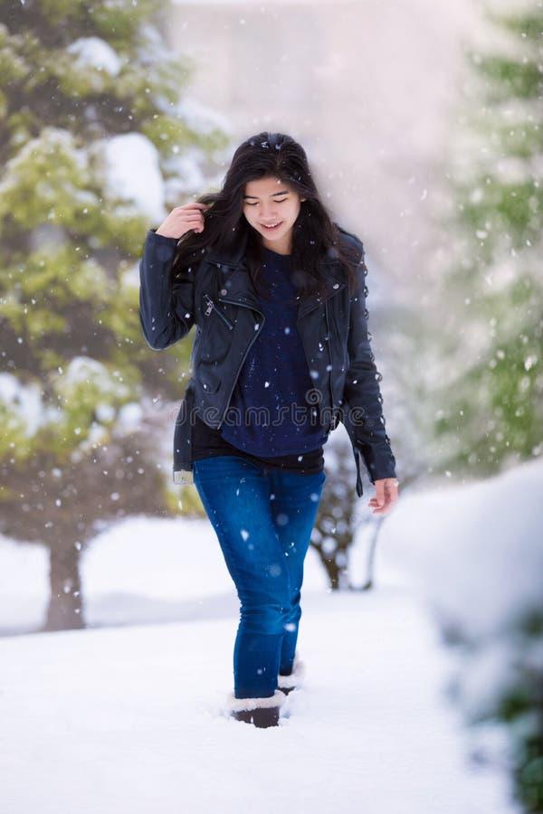 Muchacha adolescente que camina a través de yarda en nevadas fuertes imagenes de archivo