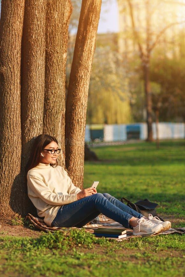 Muchacha adolescente que charla en el teléfono, sentándose debajo de árbol imagen de archivo libre de regalías