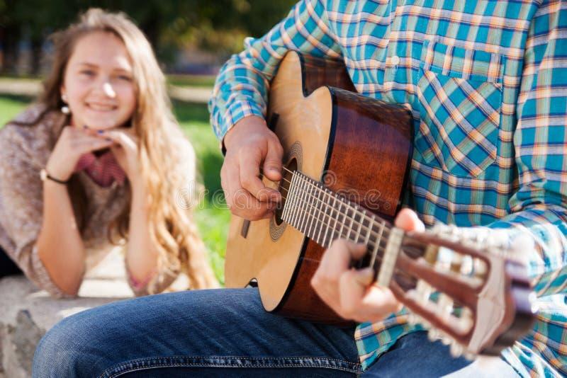 Muchacha adolescente que escucha la guitarra fotografía de archivo libre de regalías