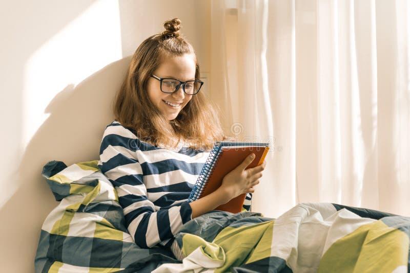 Muchacha adolescente que estudia en casa sentarse en cama Hace notas en cuaderno, se prepara para los exámenes en la escuela fotografía de archivo