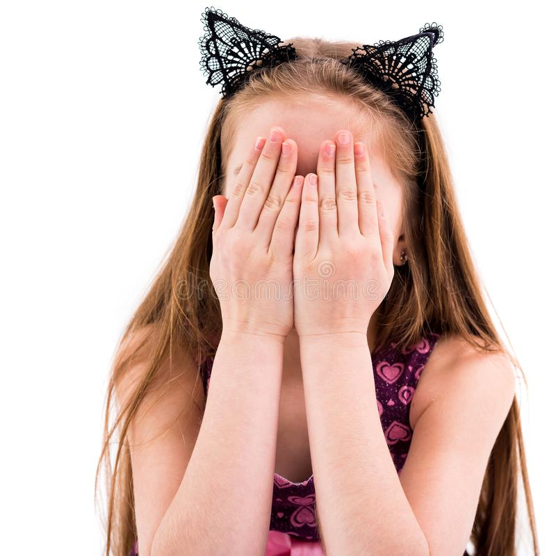 Muchacha adolescente que juega el escondite, cubriendo su cara foto de archivo libre de regalías