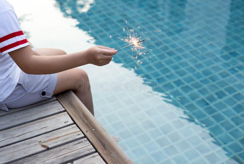 Muchacha adolescente que juega la bengala por la piscina imagen de archivo libre de regalías