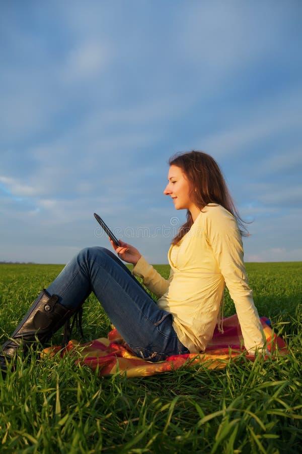 Muchacha adolescente que lee el libro electrónico al aire libre foto de archivo