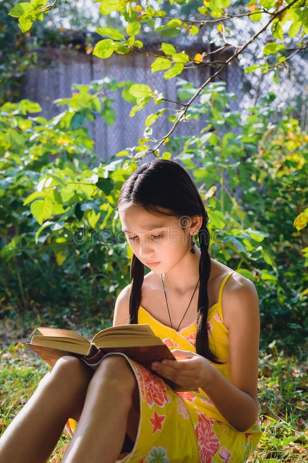 Muchacha adolescente que lee un libro en el jardín fotos de archivo libres de regalías