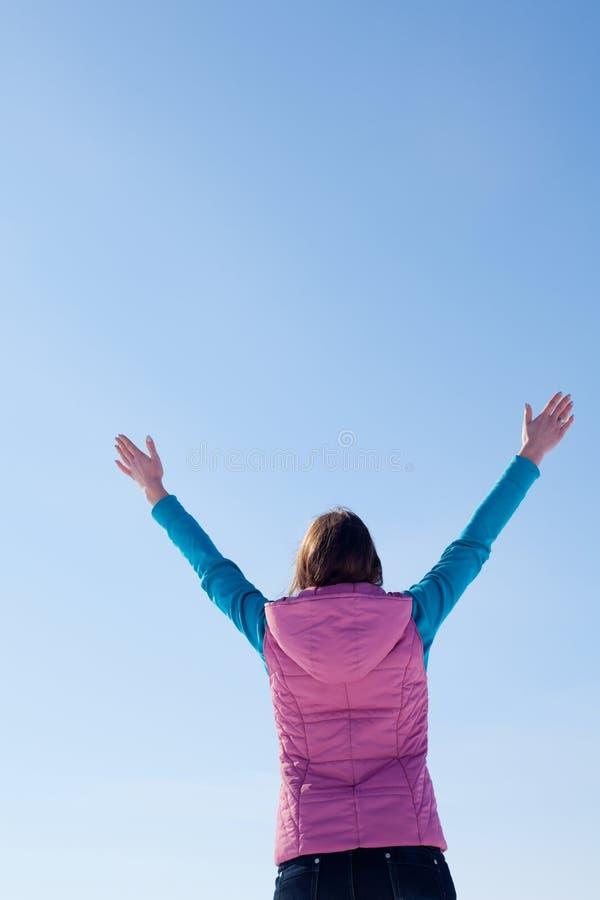 Muchacha adolescente que permanece con las manos levantadas imagen de archivo