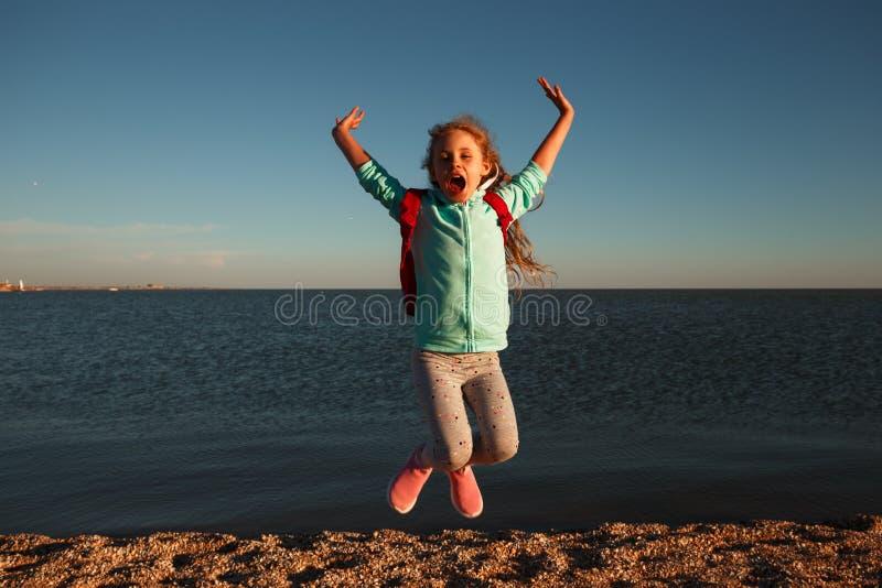 Muchacha adolescente que salta en la playa en la puesta del sol imágenes de archivo libres de regalías