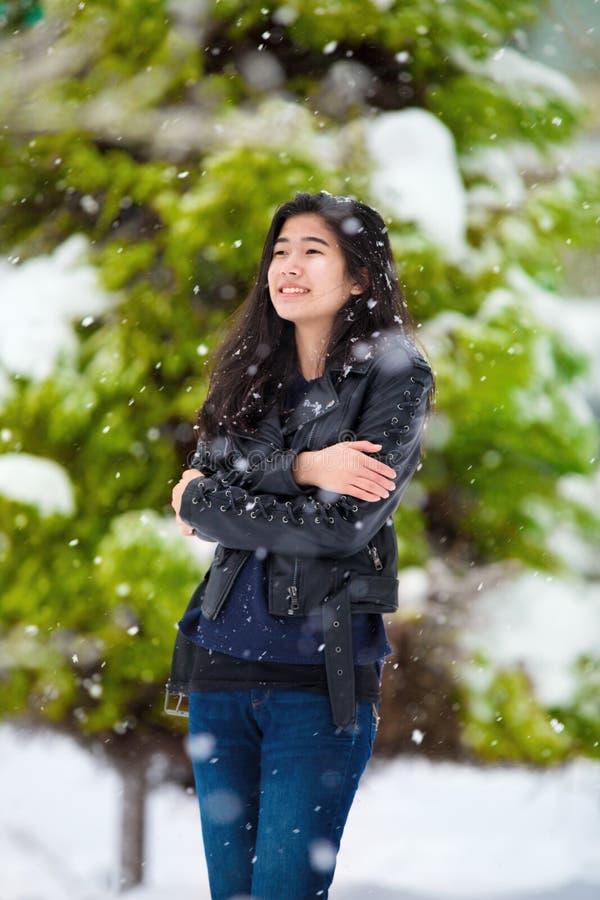 Muchacha adolescente que se coloca al aire libre en las nevadas del invierno que tiemblan de frío fotos de archivo libres de regalías