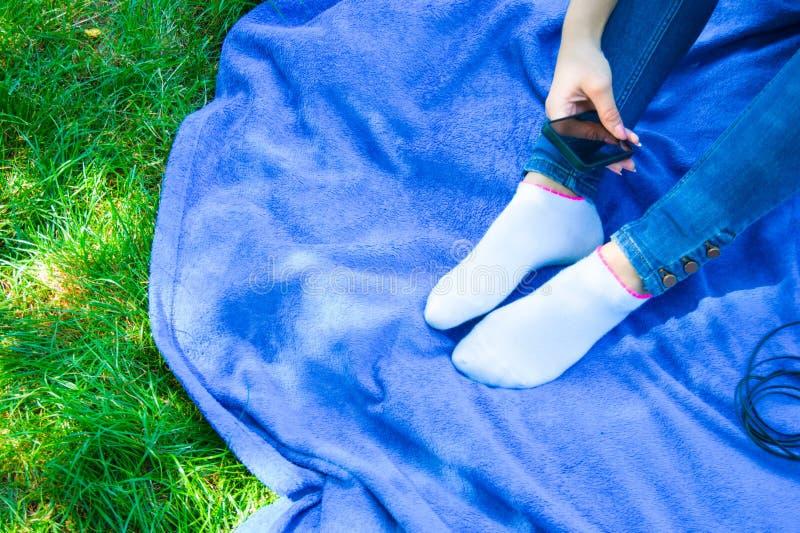 Muchacha adolescente que se sienta con un teléfono móvil a disposición en el parque fotos de archivo libres de regalías