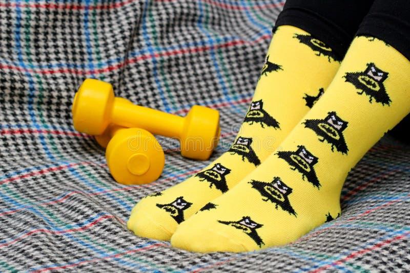 Muchacha adolescente que se sienta en el sof? Calcetines amarillos con el modelo negro de Batman dumbbells Vista lateral fotos de archivo libres de regalías