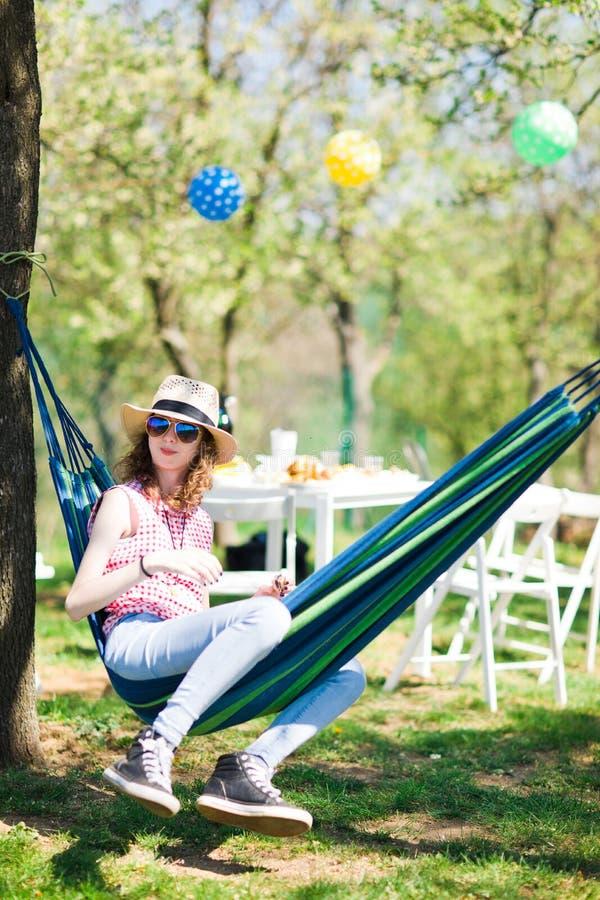 Muchacha adolescente que se sienta en hamaca en la fiesta de jardín y que come la torta fotografía de archivo