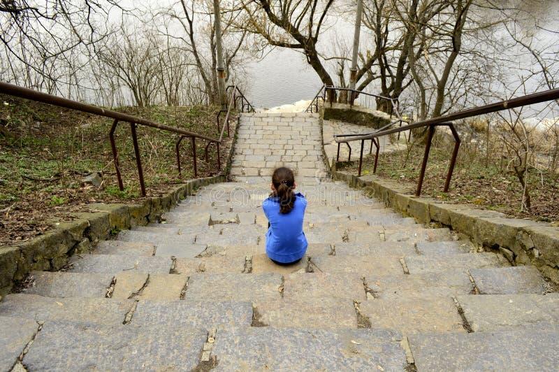 Muchacha adolescente que se sienta en los pasos foto de archivo