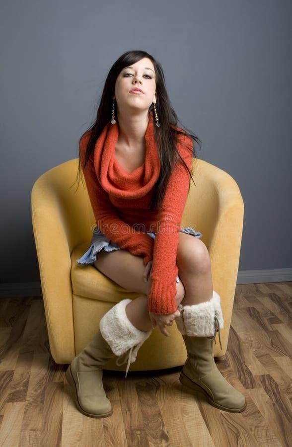 Muchacha adolescente que se sienta en silla foto de archivo libre de regalías