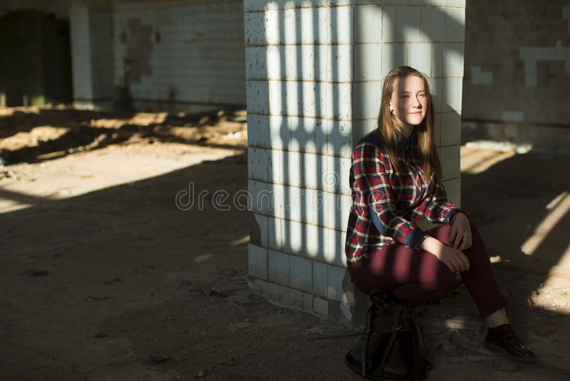 Muchacha adolescente que se sienta en un edificio abandonado en los rayos de la luz El caminar fotografía de archivo