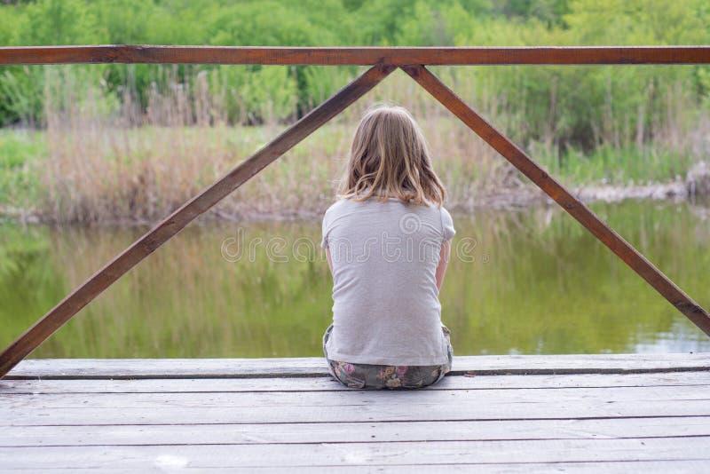 Muchacha adolescente que se sienta en un puente de madera cerca del río foto de archivo libre de regalías