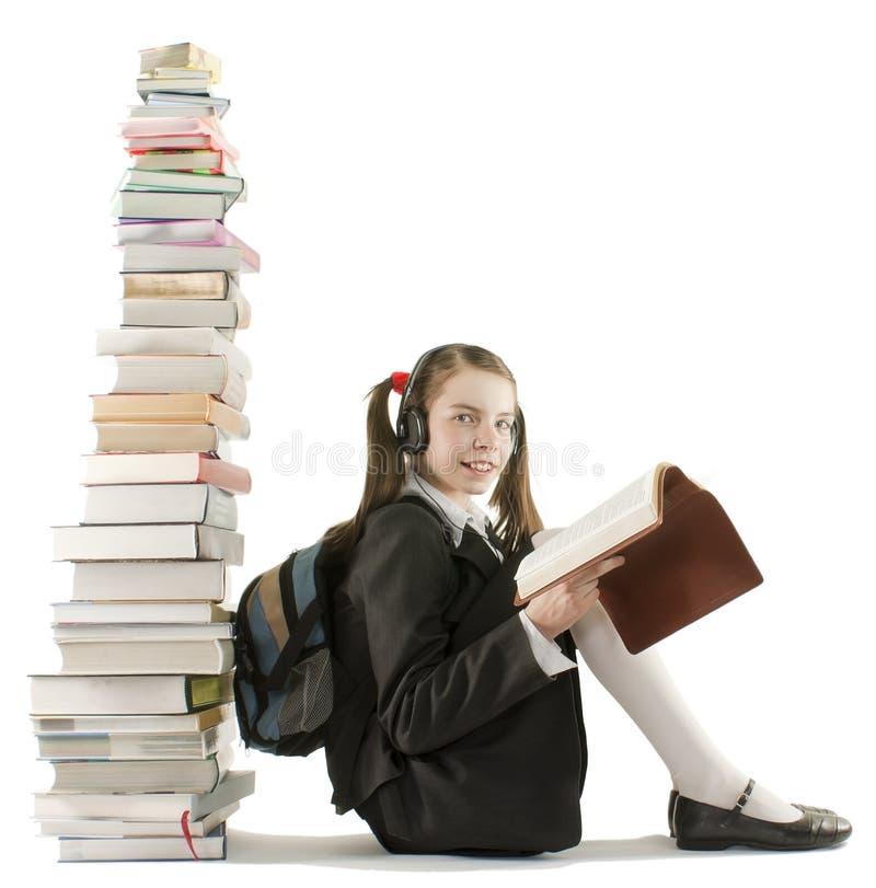 Muchacha adolescente que se sienta en una pila de libros foto de archivo