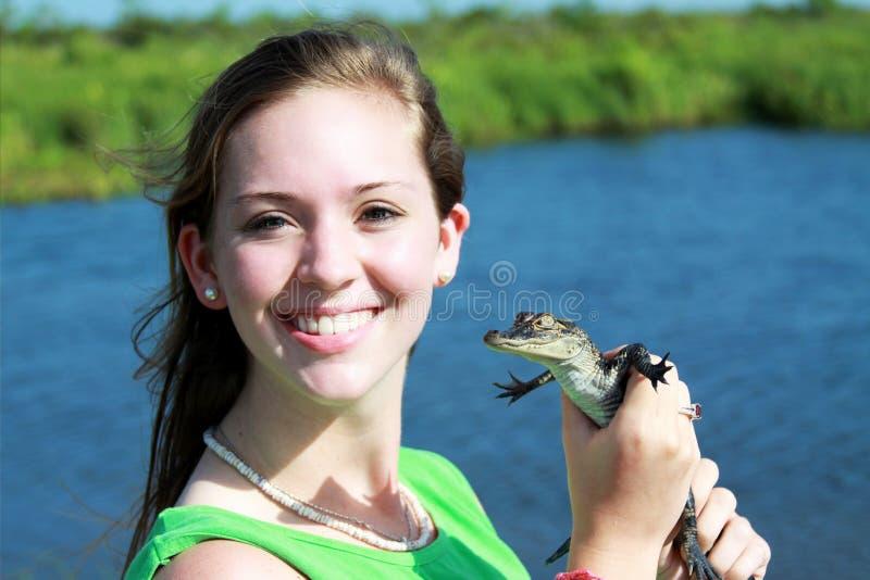 Muchacha adolescente que sostiene un cocodrilo del bebé fotos de archivo