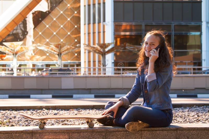 muchacha adolescente que tiene una charla del teléfono móvil en una metrópoli fotos de archivo