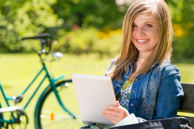 Muchacha adolescente que usa el ordenador de la tableta en parque foto de archivo