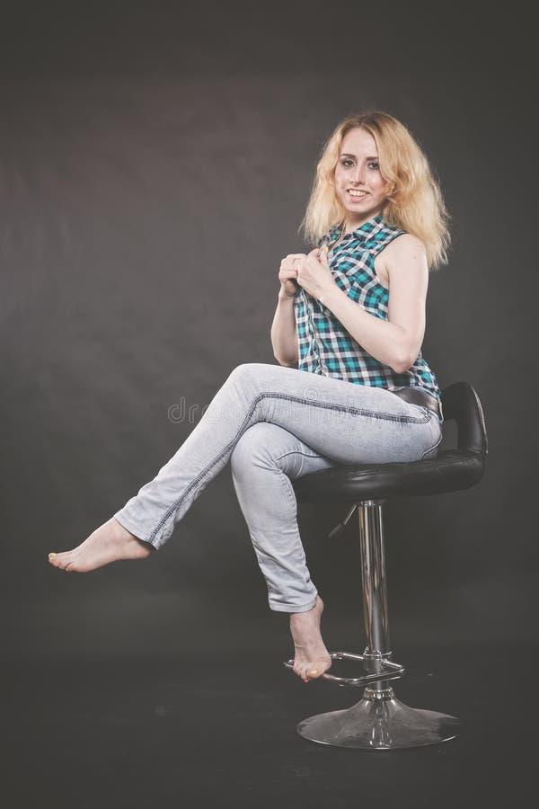 Muchacha adolescente rubia bonita que lleva la camisa a cuadros y los tejanos en la silla en fondo negro foto de archivo libre de regalías