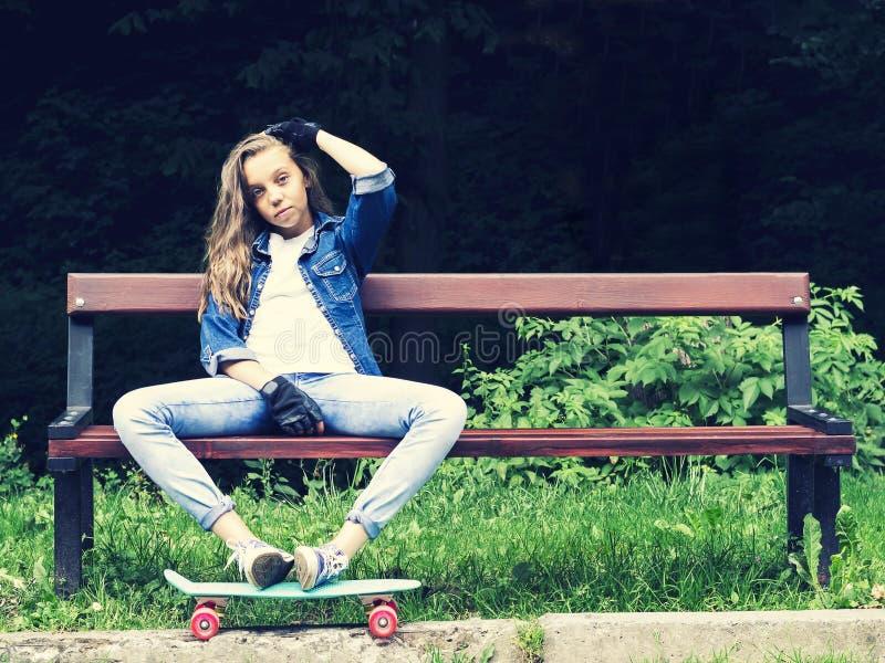 Muchacha adolescente rubia hermosa en camisa de los vaqueros, sentándose en banco con la mochila y el monopatín en parque imagen de archivo